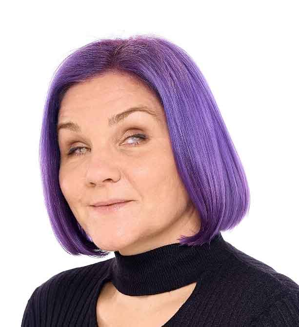Léonie is photographed smiling against a white background. She is dressed in black, her bobbed hair is dyed bright purple.