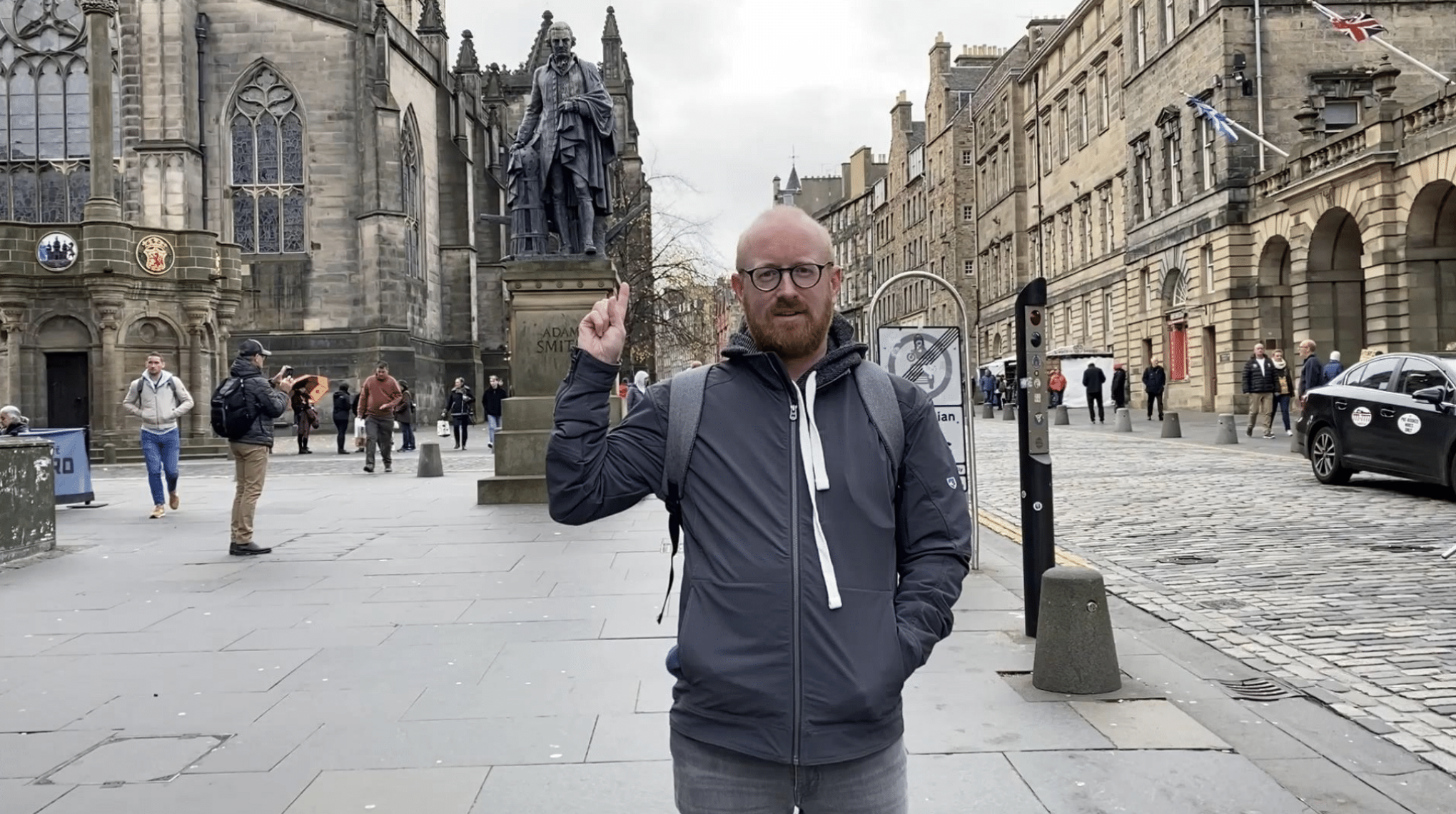 Matt May standing on the Royal Mile in Edinburgh points at the Adam Smith statue.